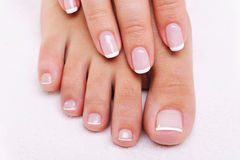 Beauty nails of a female hand and feet royalty free stock photography