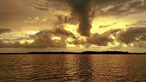 Orange colored cumulonimbus cloud, coastal, sunset seascape. royalty free stock photography