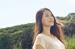 Beauty in nature with wind blown hair. Young Chinese beauty smiling in nature with wind blown hair stock photography