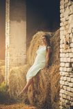 Beauty of a new life. Cheerful pregnant woman sitting on hay. Copy space royalty free stock photo