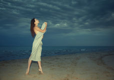 Beauty at the night beach. Nifty lady covered by towel standing at the night beach stock image