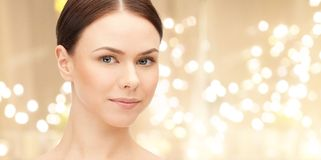 Face of beautiful woman over lights background stock image