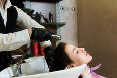 Beauty and people concept - happy young woman with hairdresser washing head at hair salon royalty free stock photography