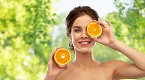 Smiling woman with oranges over grey background stock image