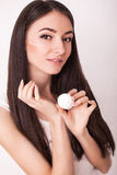 Beauty, people, cosmetics, skincare and health concept - happy smiling young woman applying cream to her face Stock Photo