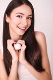 Beauty, people, skincare and cosmetics concept - happy young woman with moisturizing cream on hand and facial Royalty Free Stock Photography