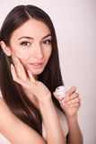 Beauty, people, skincare and cosmetics concept - happy young woman with moisturizing cream on hand and facial Stock Photography