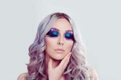 Woman with artistic purple blue eyes makeup feather on eyelashes touching face with hand royalty free stock image