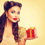 Beauty pin up girl with holiday gift box. In her hand Royalty Free Stock Images