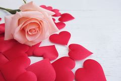 Beauty pink-orange rose and red satin hearts shape on wooden floor. Valentine's day background concept. Copy space for text stock photo