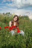 A beauty in a poppy field 5. A blond beautiful young girl sitting in poppy field on a sunny day Stock Photos