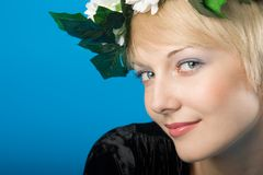 Beauty portrait. Portrait of beautiful blondie woman with floral diadem on her head and playful eyes Royalty Free Stock Image