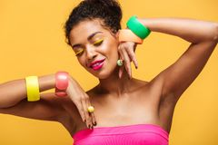 Beauty portrait of attractive african american woman with fashion makeup and jewelry on hands posing isolated, over yellow. Beauty portrait of attractive african stock image