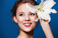 Beauty portrait of attractive, fresh woman with the lily flower on blue Stock Photos