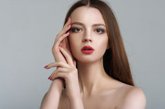 Beauty portrait of an attractive girl who folded her hands near. Her head. She has long hair and a bright make-up Stock Image