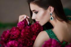 Beauty portrait. Beautiful woman with sensual maroon lips lying among peony flowers. Cosmetics, make-up. Perfumery. Stock Photo
