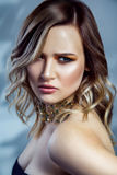 Beauty portrait of beautiful fashion model with makeup, colored wavy hairstyle and accessories on her neck. Royalty Free Stock Photos