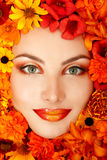 Beauty portrait of beautiful female face with orange flowers Stock Photography