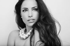 Beauty portrait. Beautiful long hair brunette wearing pearl necklace, black and white portrait royalty free stock image