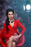 Beauty portrait of a beautiful brunette in a red dress on a gray background. royalty free stock photography