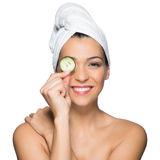 Beauty Portrait Of Beautiful Woman Holding Slice Of Cucumber Over Eye. Beauty Portrait Of Smiling Woman With Towel On Head And Slice Of Cucumber In Hand Isolated royalty free stock images