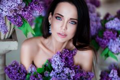 Beauty portrait. Beautiful woman with sensual lips sitting among violet flowers. Cosmetics, make-up. Perfumery. Royalty Free Stock Images