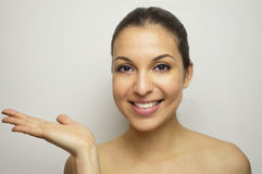 Beauty portrait of beautiful woman showing beauty product / empty copy space on open hand palm. Royalty Free Stock Images