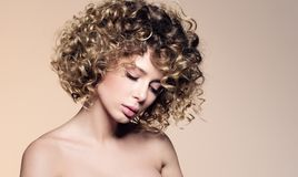 Beauty portrait of beautiful young woman with closed eyes. Hairstyle with curly hair royalty free stock photo