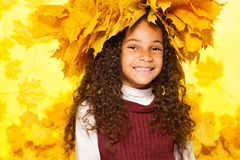 Beauty portrait of black girl in maple wreath. Beauty portrait of little black girl with wreath made of orange autumn leaves with big smile on her face with big Stock Photos