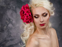 Beauty portrait of a blonde with a big red flower in her hair Stock Photo