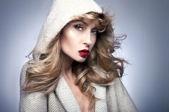 Beauty portrait of blonde woman in hood. Royalty Free Stock Photography