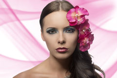 Pretty brunette with flowers near face . FLOWERS ARE FAKE Stock Photo