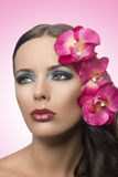 Pretty brunette with fake flowers Stock Photos