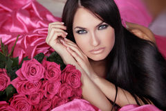 Beauty portrait of brunette girl with pink Roses lying on the be Stock Images