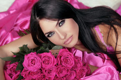 Beauty portrait of brunette girl with pink Roses lying on the be Stock Image