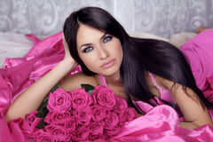 Beauty portrait of brunette girl with pink Roses lying on the be Royalty Free Stock Photos