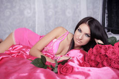 Beauty portrait of brunette girl with pink Roses lying on the be Stock Photo