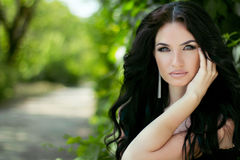 Beauty portrait of brunette model woman posing on nature backgro Royalty Free Stock Image