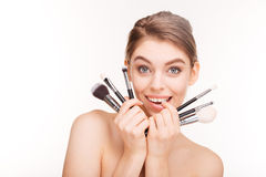 Beauty portrait of cute lovely young woman holding makeup brushes. Near her face over white background Royalty Free Stock Photo