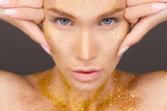 Beauty portrait of cute lovely young woman. With sparkles on her face on gray background Royalty Free Stock Images