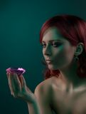 Beauty portrait with diamond. Beauty portrait of woman with big pink diamond on dark background Royalty Free Stock Images