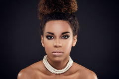 Beauty portrait of elegant african american woman. Closeup beauty portrait of elegant african american girl wearing pearls. Glamour makeup. Creative hairstyle Stock Photography