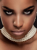 Beauty portrait of elegant african american woman. Closeup beauty portrait of elegant african american girl wearing pearls. Glamour makeup. Creative hairstyle Royalty Free Stock Photography