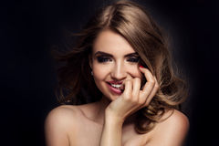 Beauty portrait of elegant woman. Beauty portrait of smiling pretty woman. Dark background. Girl looking at camera. Glamour makeup Stock Photo