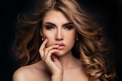 Beauty portrait of elegant woman. Beauty portrait of elegant young woman. Dark background. Girl looking at camera. Glamour makeup. Naked shoulders. Ideal skin Stock Photography