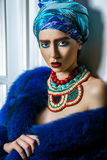 Beauty portrait of fashion model with colored headwear, blue fur coat red eyebrow and lips makeup and necklace. Studio shot near windows and white wall Stock Image