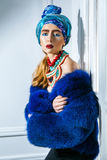 Beauty portrait of fashion model with colored headwear, blue fur coat red eyebrow and lips makeup and necklace. Studio shot near windows and white wall Royalty Free Stock Photo