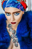 Beauty portrait of fashion model with colored headwear, blue fur coat red eyebrow and lips makeup and necklace. Studio shot near windows and white wall Stock Images