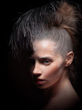 Beauty portrait  with feather on dark. Royalty Free Stock Photography