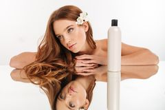 Beauty portrait of ginger woman with flower in hair. Reclines on mirror table with bottle of lotion over grey background Royalty Free Stock Image